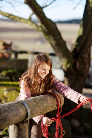 reins: Girl tying red reins to the wooden fence of the paddock Stock Photo