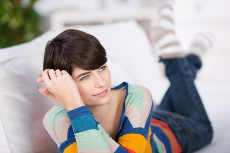 thinks: Beautiful young female looking at something on couch Stock Photo