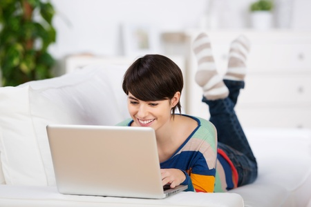 Happy woman browsing on her laptop at the living room photo