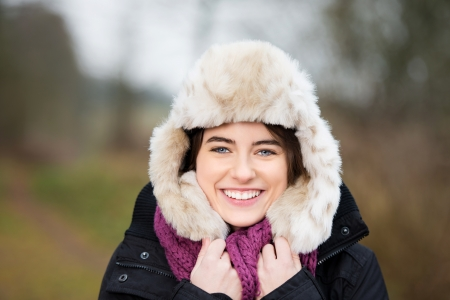 overcoat: Portrait of a smiling woman with fur hat Stock Photo