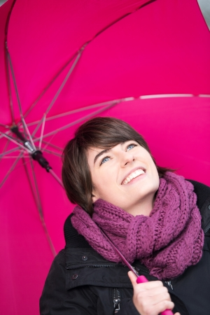 inclement: Smiling woman with a pink umbrella and scarf