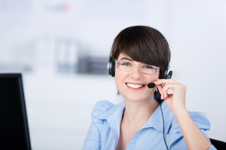 Happy female customer service representative working with headphone and computer photo