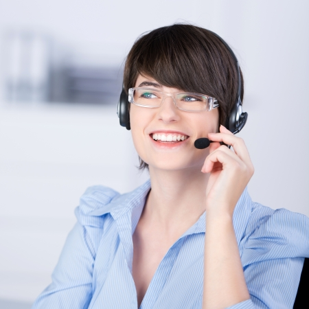 verbal communication: Pretty young brunette and professional woman wearing glasses, talking on the phone using headsets