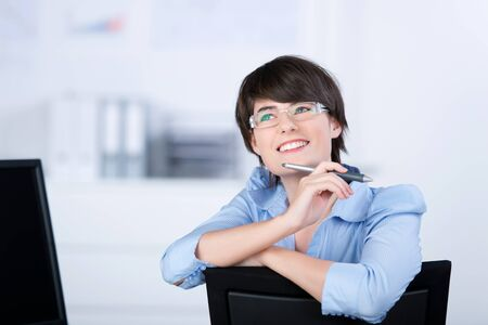 formals: Portrait of a modern female worker sitting on a black chair Stock Photo