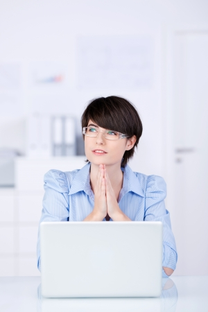 Pensive young woman at the office sitting behind her laptop looking off into space photo
