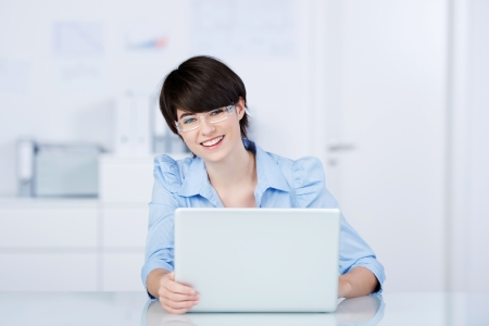 Smiling successful woman with a laptop looking at the camera while seated at her desk photo