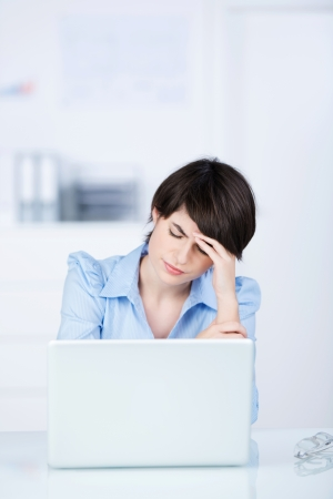 wornout: A young businesswoman sits behind her laptop computer frowning with her head in her hands because of a problem at work