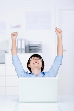 fair skin: Retrato de la mujer exitosa alzando las manos en la oficina