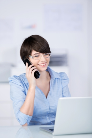 Motivated attractive young woman talking on a telephone in the office with a lovely smile on her face photo