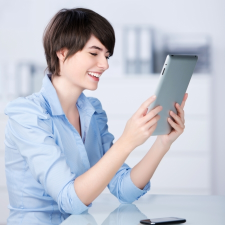 Beautiful young businesswoman with a lovely smile reading a tablet computer while sitting in the office Stock Photo - 21147821