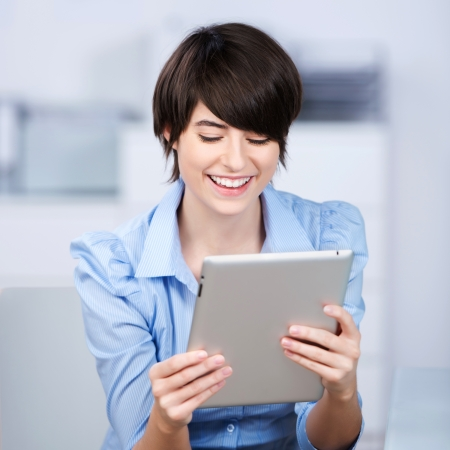 Happy young woman reading a tablet which she is handholding, upper body portrait in an office Stock Photo - 21147822