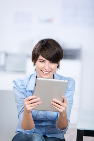 Smiling female sitting and holding a digital tablet Stock Photo - 21147823