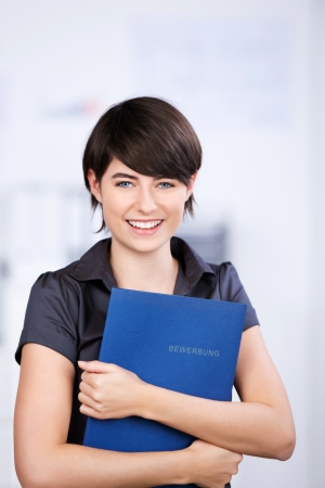 fair skin: Happy young applicant holding a portfolio in a close up shot