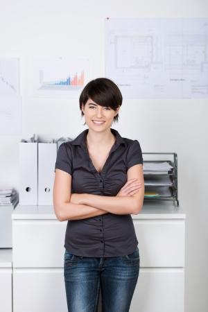 fair skin: Mujer feliz de pie con los brazos cruzados en la oficina