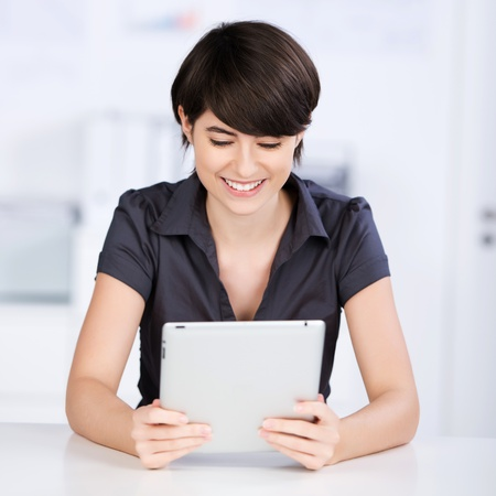 Pretty woman reading her tablet-pc while sitting at a table in the office Stock Photo - 21147847