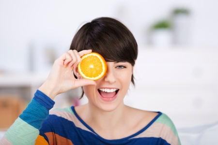 ripeness: Cheerful female holding a healthy slice of citrus fruit Stock Photo