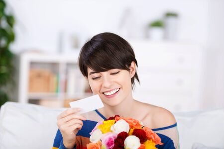 Beautiful woman with a gift of flowers smiling as she reads the accompanying card photo