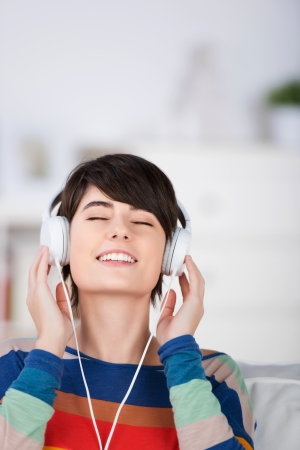 listening back: Young woman enjoying her music sitting with her eyes closed and head tilted back listening to her headphones Stock Photo