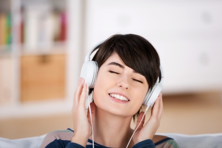appreciation: Beautiful woman enjoying listening music wearing a set of headphones and sitting with her eyes closed in ecstasy Stock Photo