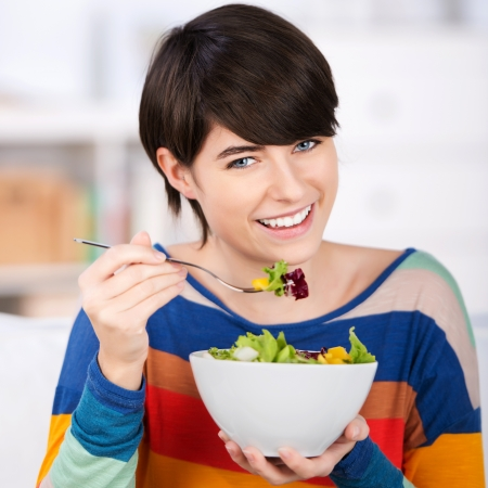 新鮮なおいしい緑豊かなグリーン サラダのボウルで健康的な食事を食べる女性