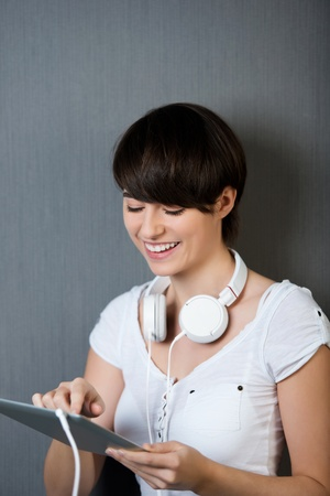 Woman ordering music over the internet scrolling with her finger on the touchscreen of her tablet photo
