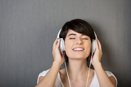 bliss: Head and shoulders studio portrait of a young woman listening to music on a set of headphones standing with her eyes closed in bliss Stock Photo