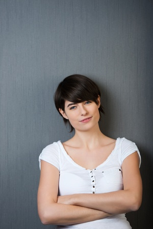 Arms crossed female posing and leaning on a grey wall photo