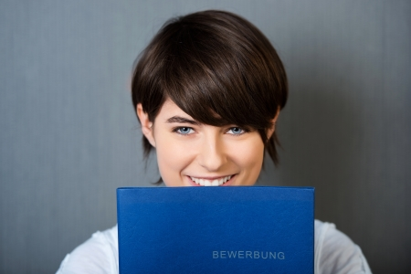 applicant: Smiling female applicant holding blue document in a close up shot