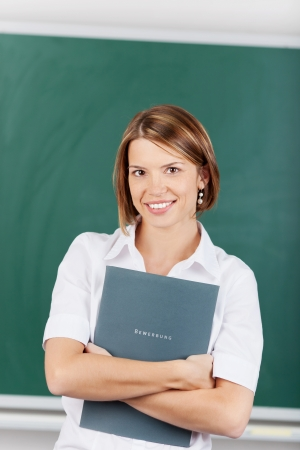 Beautiful teacher holding a lesson plan inside the classroom photo