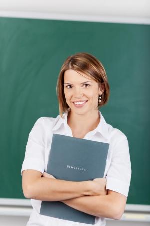 Beautiful teacher holding a lesson plan inside the classroom photo