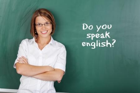 docenten: Vrolijke vrouw onderwijs Engels klasse in de klas Stockfoto