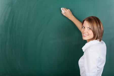 weiblich: Lächelnd weibliche Lehrer mit einem Kreide und Schreiben an der Tafel