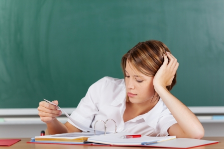 angry blonde: Portrait of teacher thinking and looking on her lesson plan