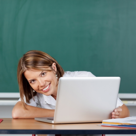Smiling teacher posing with laptop on the table at the classroom Stock Photo - 21148126