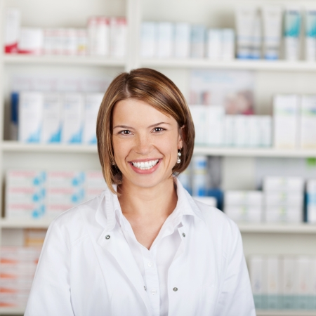 big smile: Portrait of a smiling female pharmacist with a beautiful big smile standing in her pharmacy