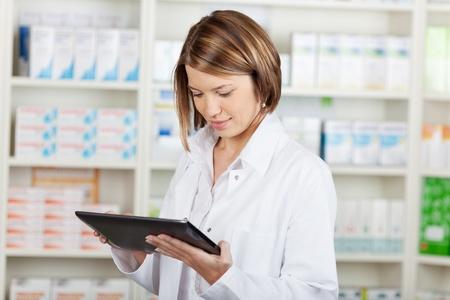 farmacia: Farmac�utico que trabaja con un tablet-PC en la farmacia sosteni�ndolo en la mano durante la lectura de la informaci�n Foto de archivo