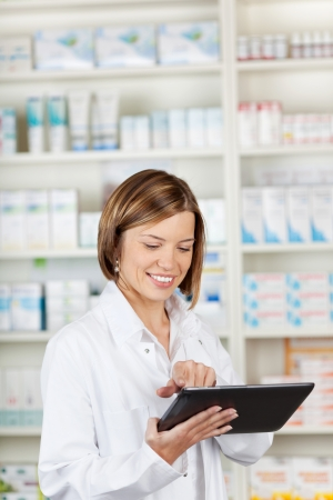 Smiling pharmacist using a tablet-pc scrolling with her finger on the touchscreen while standing in front of shelves of medication photo