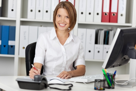 formals: Smiling confident businesswoman sitting at her desk in the office in front of a desktop computer