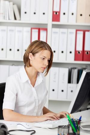 trabajo en la oficina: Mujer que trabaja en una computadora de escritorio en su oficina para concentrarse en la lectura de la informaci�n en la pantalla mientras se escribe Foto de archivo