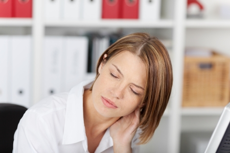 Woman with a stiff painful neck rubbing the back of her head with her hand and grimacing in pain photo