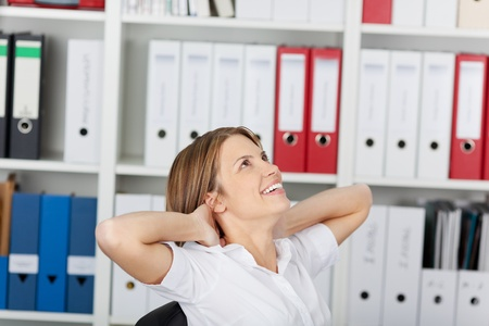 arm chair: Happy woman relaxing in the office sitting back in her chair, hands behind her neck
