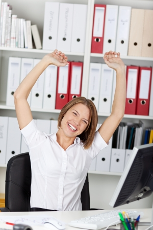 formals: Excited triumphant woman rejoicing raising her arms in the air and laughing and cheering in her office