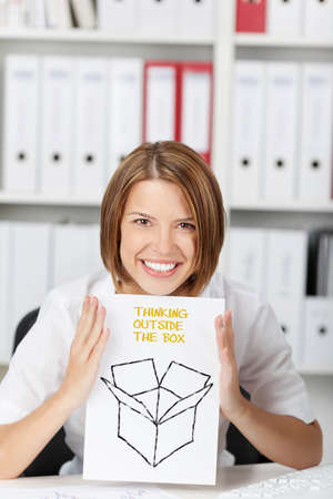 Businesswoman write on paper - Think Outside The Box at office photo