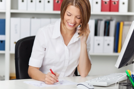 office phone: Beautiful young businesswoman calling by phone while writing on white paper at office Stock Photo