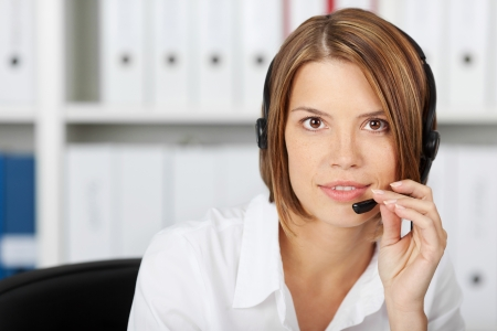 Confident businesswoman talking on headset in the office photo
