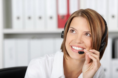 telephony: Positive smiling businesswoman talking on headset in the office