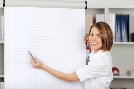 formals: Attractive smiling young woman writing on a blank flipchart in an office as she does a presentation or promotion