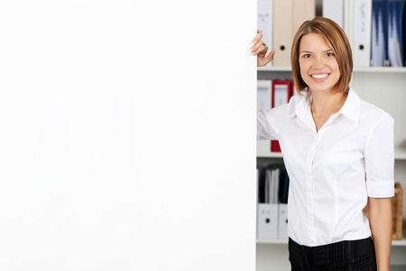 formals: Smiling woman with blank white flipchart while standing alongside it in the office