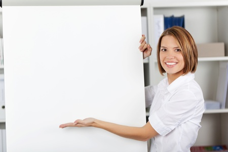 Smiling woman pointing to a a blank white flipchart with her hand while standing alongside it in the office photo