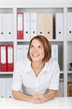 formals: Pretty businesswoman sitting thinking looking up into the air at her desk at the office